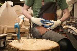 Carpenter shaping wood with worktool