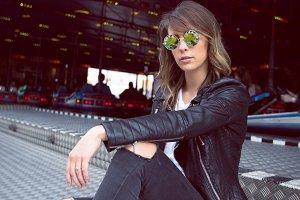 Beautiful woman wearing sunglasses sitting against bumper cars ride