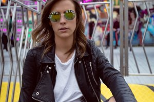 Woman wearing leather jacket and sunglasses sitting against ride