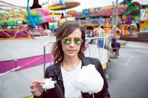 Young woman wearing sunglasses holding cotton candy against ride