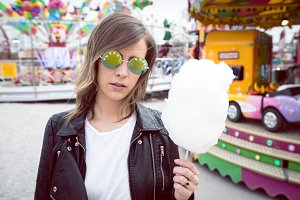 Woman wearing sunglasses holding cotton candy against rides