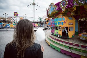 Rear view of woman holding cotton candy by carousel