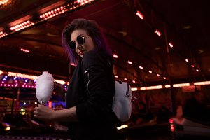 Side view of young woman holding cotton candy against illuminated ride