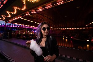 Young woman wearing sunglasses while holding cotton candy against illuminated ride