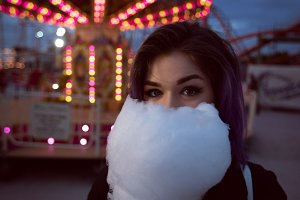 Portrait of woman holding cotton candy against illuminated carousel