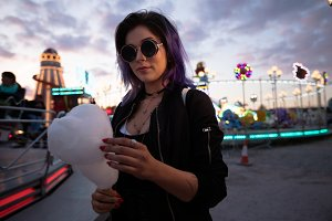 Woman wearing sunglasses holding cotton candy against sky
