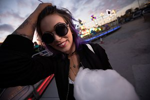 Tilt image of smiling woman wearing sunglasses standing with cotton candy