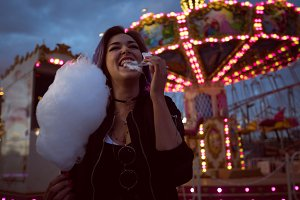 Happy woman eating cotton candy against illuminated carousel