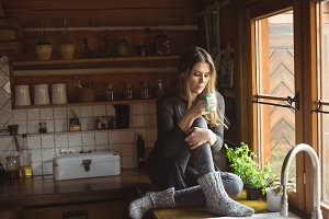 Thoughtful woman having coffee in kitchen