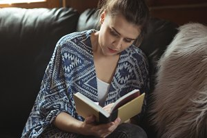 Woman reading book on sofa in living room