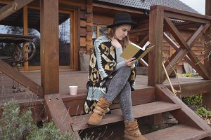 Woman reading book sitting on the porch of house
