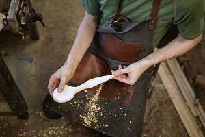 Mid section of carpenter making wooden spoon