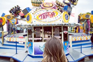 Rear view of woman standing against amusement rides