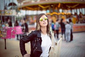 Beautiful fashionable woman wearing sunglasses against carousel