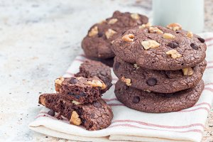 Homemade chocolate cookies with walnuts and chocolate chips on table, served with milk, horizontal, copy space
