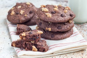 Homemade chocolate cookies with walnuts and chocolate chips on table served with milk, horizontal
