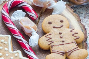 Sweet gifts for holiydays. Homemade christmas gingerbread cookies and caramel candies on wooden board, vertical