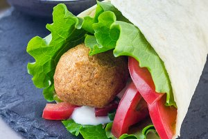 Chickpea falafel balls with vegetables and sauce, roll sandwich preparation, square