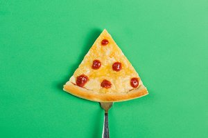 Slice of pizza on a fork on a green background