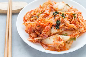 Kimchi cabbage. Korean appetizer on white plate, horizontal, closeup