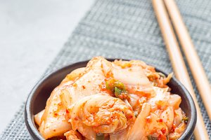 Kimchi cabbage. Korean appetizer in ceramic bowl, vertical, copy space