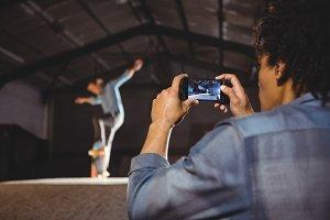 Man taking a video of skateboarding tricks