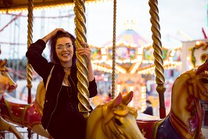 Smiling beautiful woman with hand in hair sitting on carousel horse