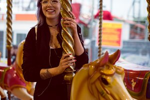 Smiling woman sitting on carousel horse