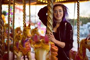 Portrait of smiling beautiful woman enjoying carousel ride