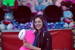 Portrait of beautiful woman wearing eyeglasses holding stuffed pink toy at funfair