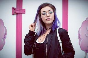 Beautiful woman wearing eyeglasses against wall