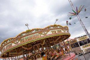 Tilt shot of chain swing ride and carousel against sky