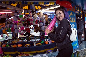 Side view portrait of smiling beautiful woman standing at stuffed toy stall