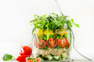 Healthy salad jar with quinoa and vegetables, cherry tomatoes, cucumber, ruccola. Raw vegetarian meal for diet, detox, clean eating. Homemade concept