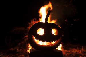 pumpkin head with a terrible smile against the background of fire