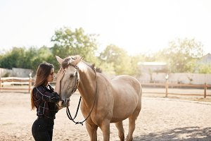 Young female horse owner taking a walk with an animal on a farm or ranch. Freedom concept.