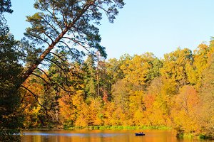 autumn forest and the lake on which the boat floats