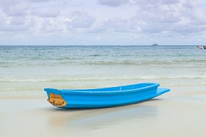 blue boat on sand beach.