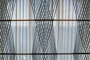 Net curtains on window with rope pattern