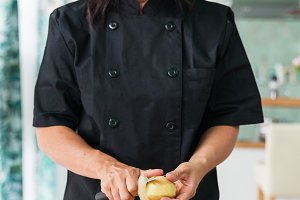 woman chef peeling a potato