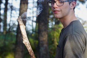 Young man holding a smoldering stick