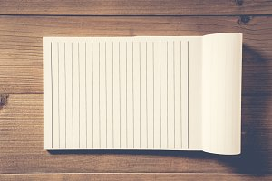 blank notebook on brown wood table