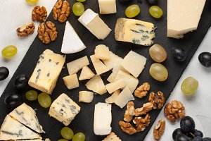 Assorted cheeses with white grapes, walnuts, crackers and white wine on a stone Board. Food for a romantic date on a light background. Top view