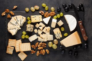 Assorted cheeses with white grapes, walnuts, crackers and white wine on a stone Board. Food for a romantic date on a dark background. Top view