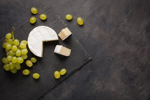 Cutting board of camembert cheese and white grapes on dark stone background. From top view with copy space
