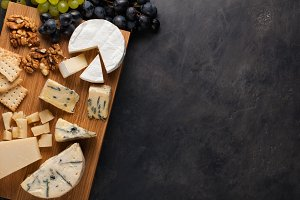 Tasting cheese dish on a wooden plate. Food for wine and romantic, cheese delicatessen on a dark stone table. Top view with copy space