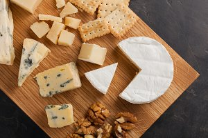 Tasting cheese dish on a wooden plate. Food for wine and romantic, cheese delicatessen on a dark stone table. Top view