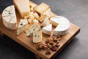 Tasting cheese dish on a wooden plate with walnuts and crackers. Food for wine and romantic, cheese delicatessen on a dark stone table