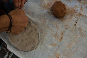 Cropped hand of craftsperson kneading clay