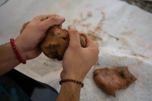 Cropped image of craftsperson making clay sculpture